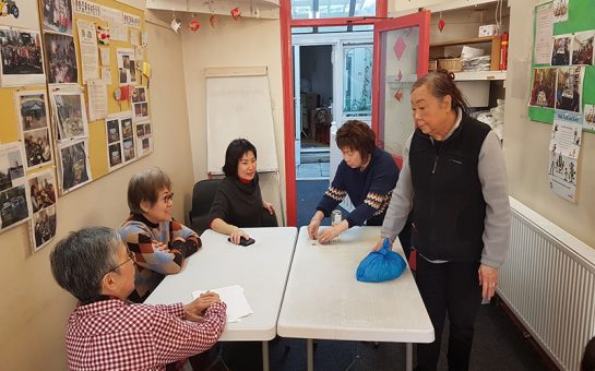 Lambeth Chinese Community association members gather around table for a meeting