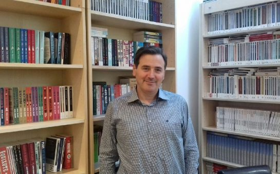 Alessandro Gallenzi in front of bookshelves at Alma Books