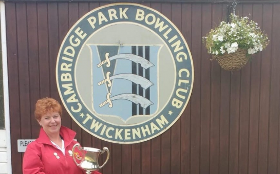 Dawn Slaughter, captain of the ladies' team at Cambridge Park Bowls Club, holding a trophy under the club's sign