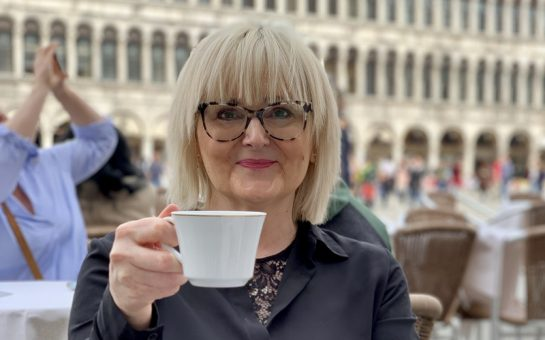 A photo of a blond woman wearing glasses, smiling and holding a tea cup.