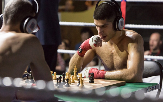 Two people playing chess with their shirts off.