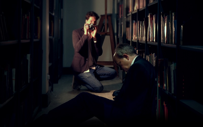 A dark scene showing a man slumped over in a corridor and a person taking a picture of him