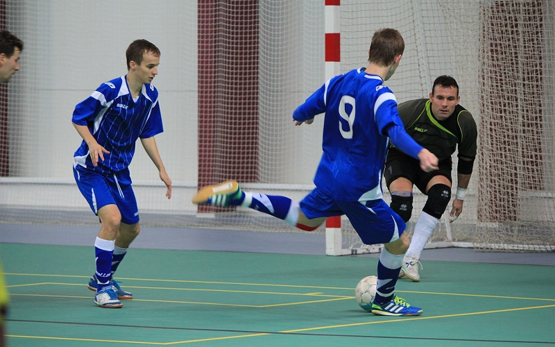 Futsal players on an indoor pitch