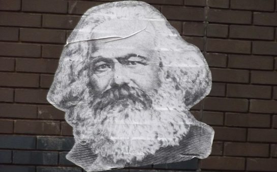 A poster of Karl Marx on a brick wall