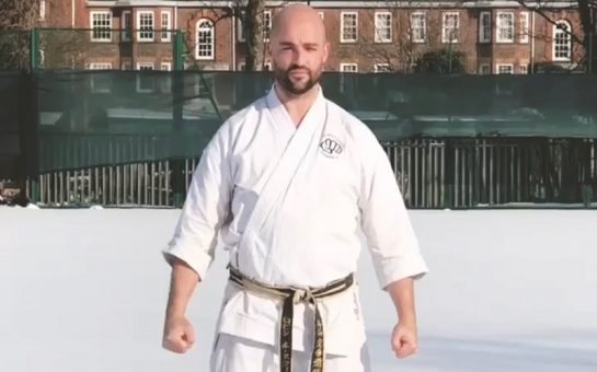 A Karate coach in white stands in snow
