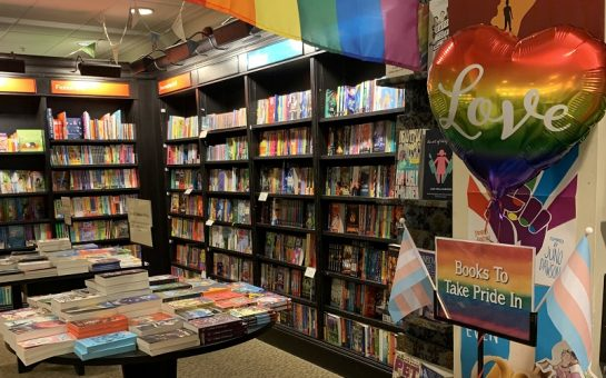 The inside of Croydon Waterstones. Shelves of books, and a display with gay and trans pride flags and a sign saying 'books to take pride in'.