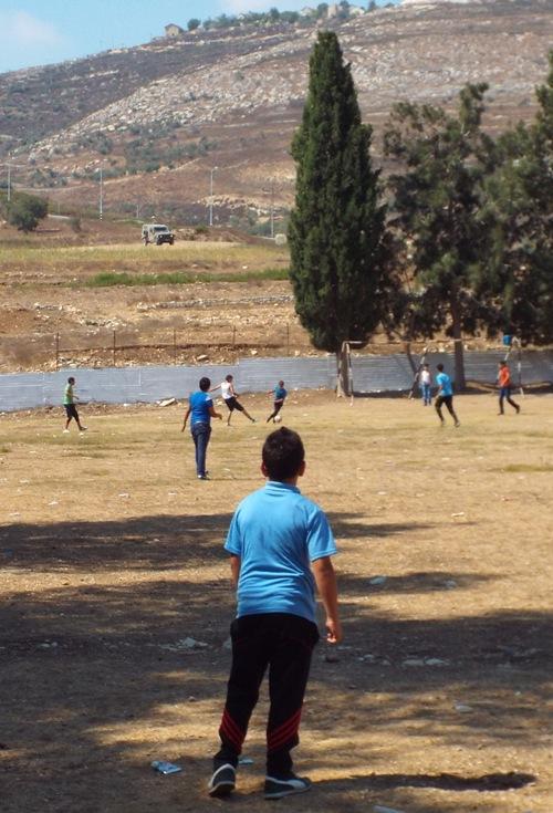 Nikki Ray  Boys playing football look towards the army jeep watching over Burin School yard