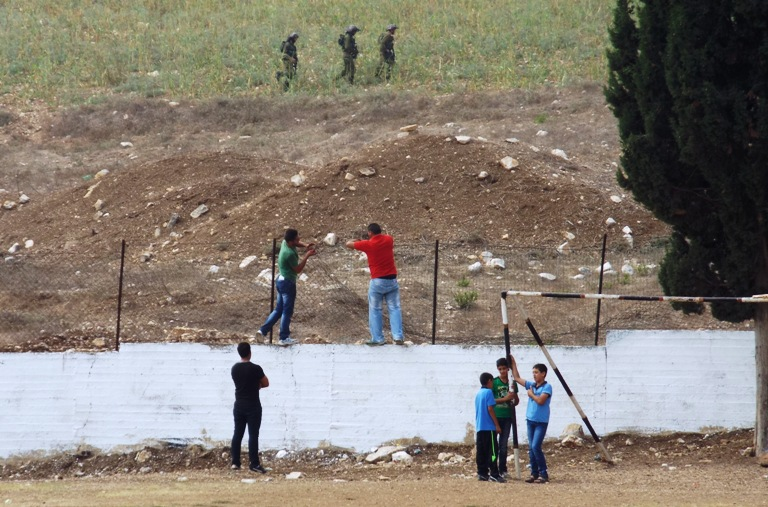 Nikki Ray  Men reinforcing the fence at Burin School whilst the Israeli army patrols above  Burin  31 08 14