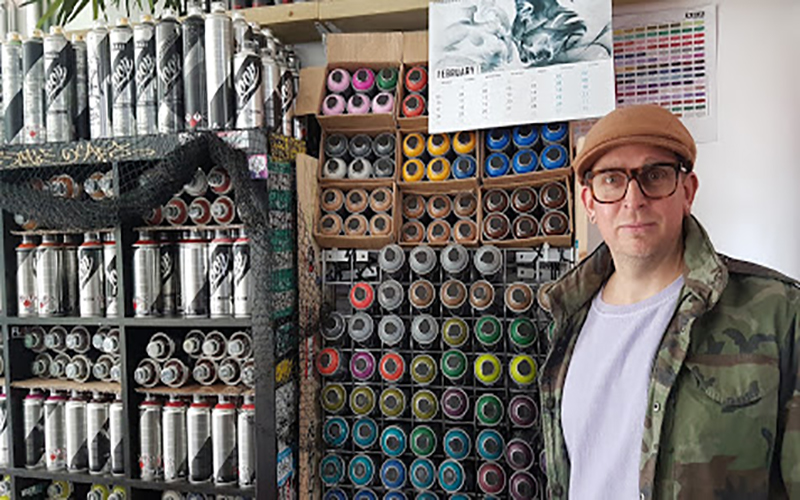 Graffiti artist and cafe owner Psych stands next to wall of spray cans