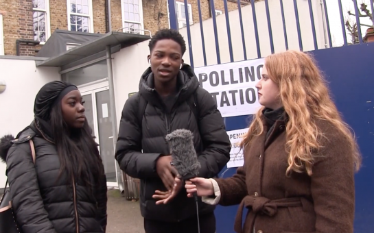 Journalist talking to two first time voters outside a polling station in Kensington