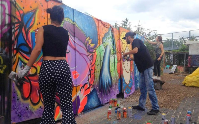 artists spray painting a wall