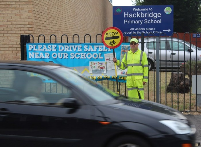 Sutton Council lollipop man children road safety crossing car passing by