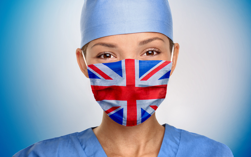 NHS doctor wearing a union jack mask on a blue background
