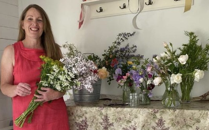 Image shows a white woman in a pink dress holding flowers and standing beside many colourful bouquets.