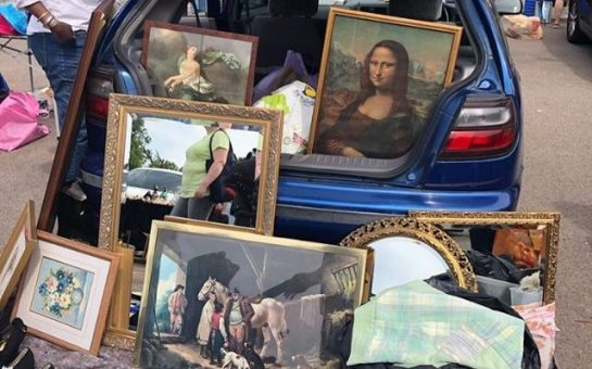 Paintings and mirrors are shown inside a car boot and on the floor next to it.