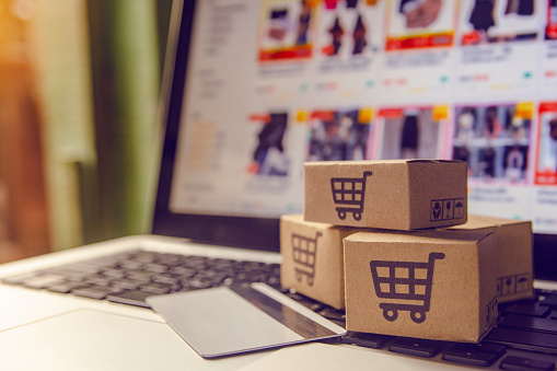 A stock image of a laptop with three little brown cardboard boxes with shopping trollies on the keyboard next to a credit card.