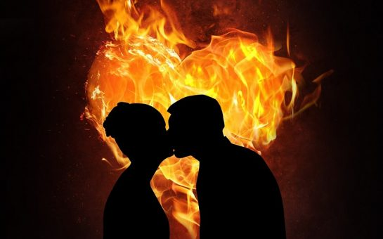 Shadow of couple kissing in front of burning heart