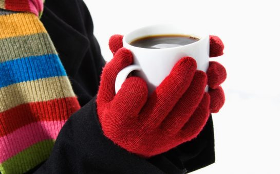 Hands in winter gloves holding mug of hot cocoa
