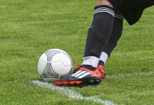 Footoballer kicking football on football pitch
