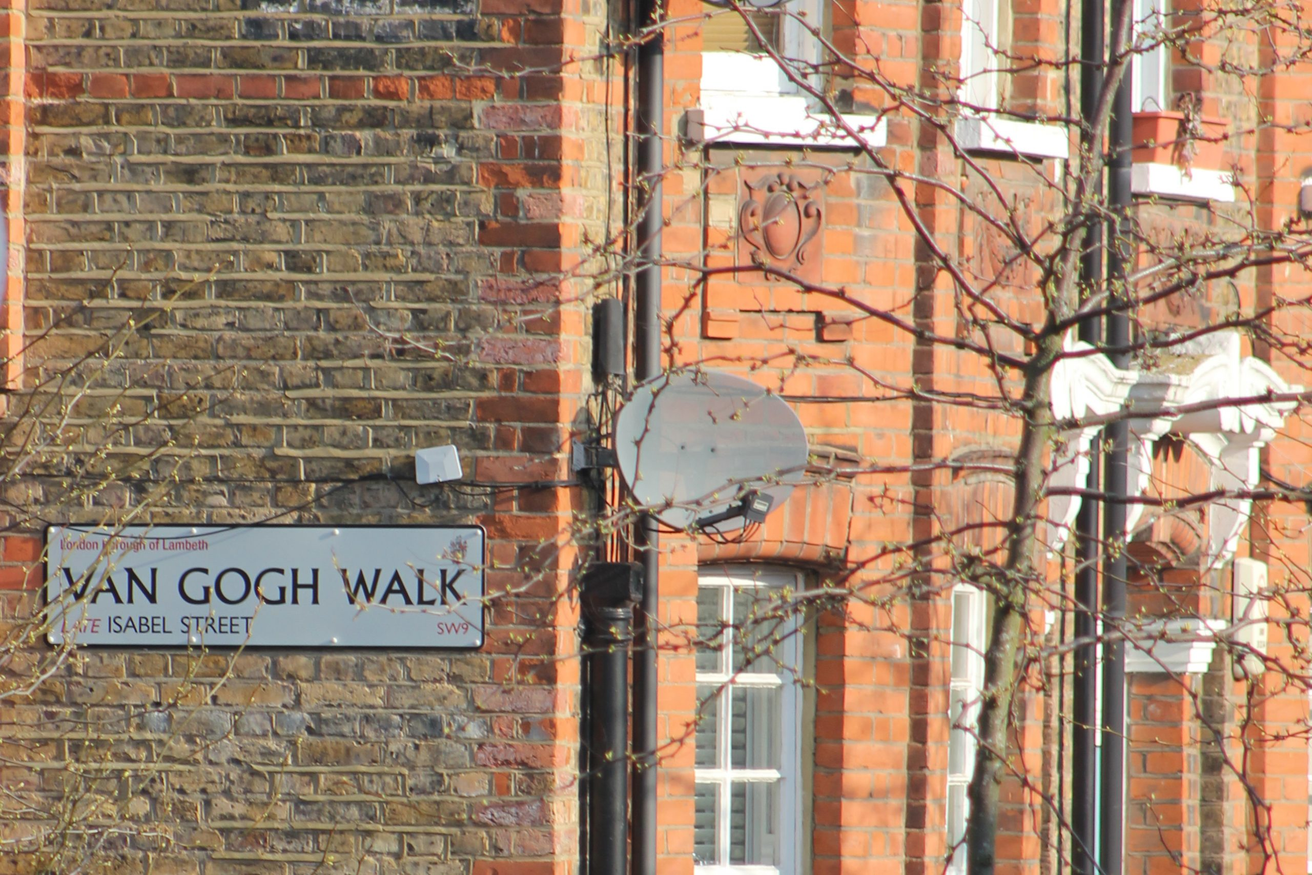 A street sign reads 'Van Gogh Walk' on a brick wall.