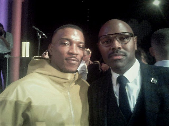 Ashley Walters, a British rapper, in a yellow coat, smiling next to Mr Gee in glasses and a smart tartan suit.