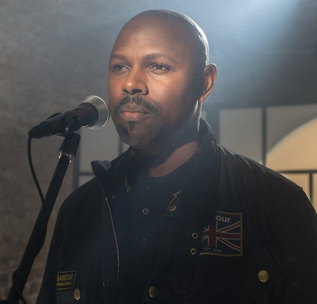 Mr Gee looking stern about to talk into a microphone. There is a spotlight on him. He is bald with a moustache and a goatee.