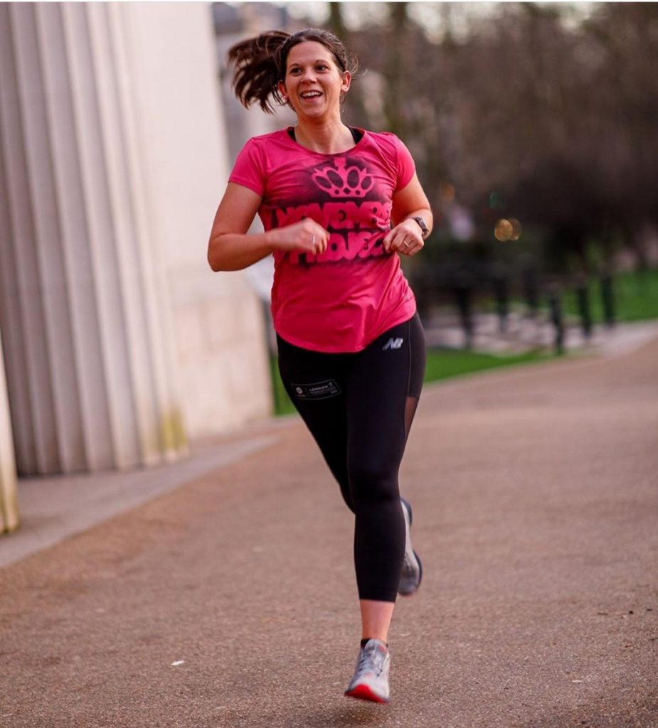 A portrait photo of Anna from The Running Channel running wearing black lycra running leggings and a pink top. She is smiling and her long dark brown pony tail is swishing in the wind.