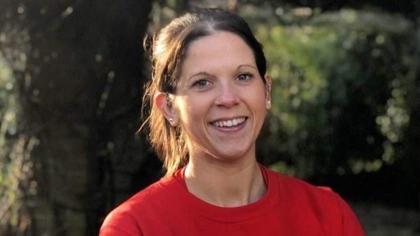 Anna from The Running Channel in a red t-shirt smiling naturally at the camera. She is outside in front of some trees and her dark brown hair is tied back.