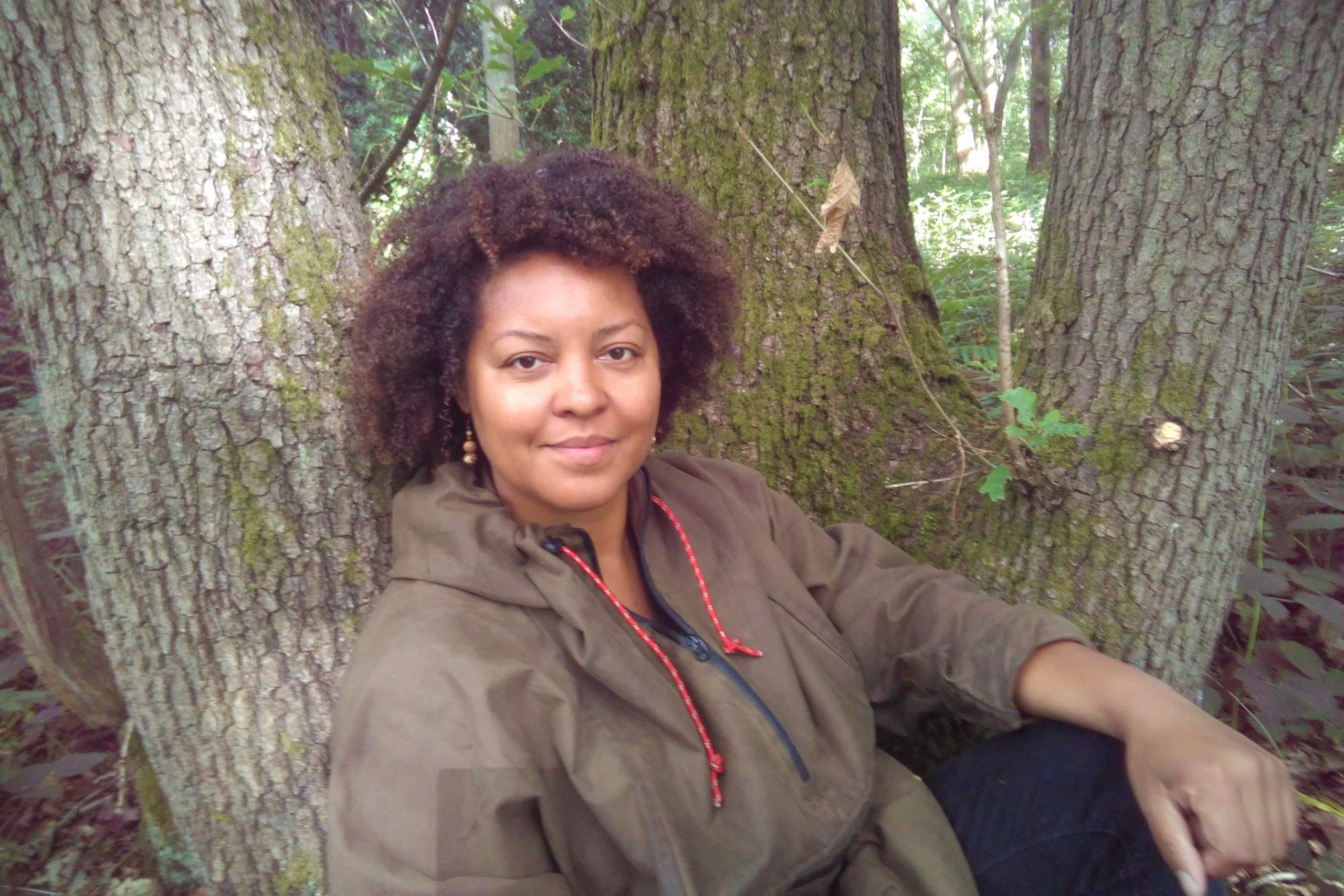 Beth sitting in front of a tree looking at the camera. She has tight curly brown hair and is wearing a dark green rain coat. Her arms is resting on her knee.