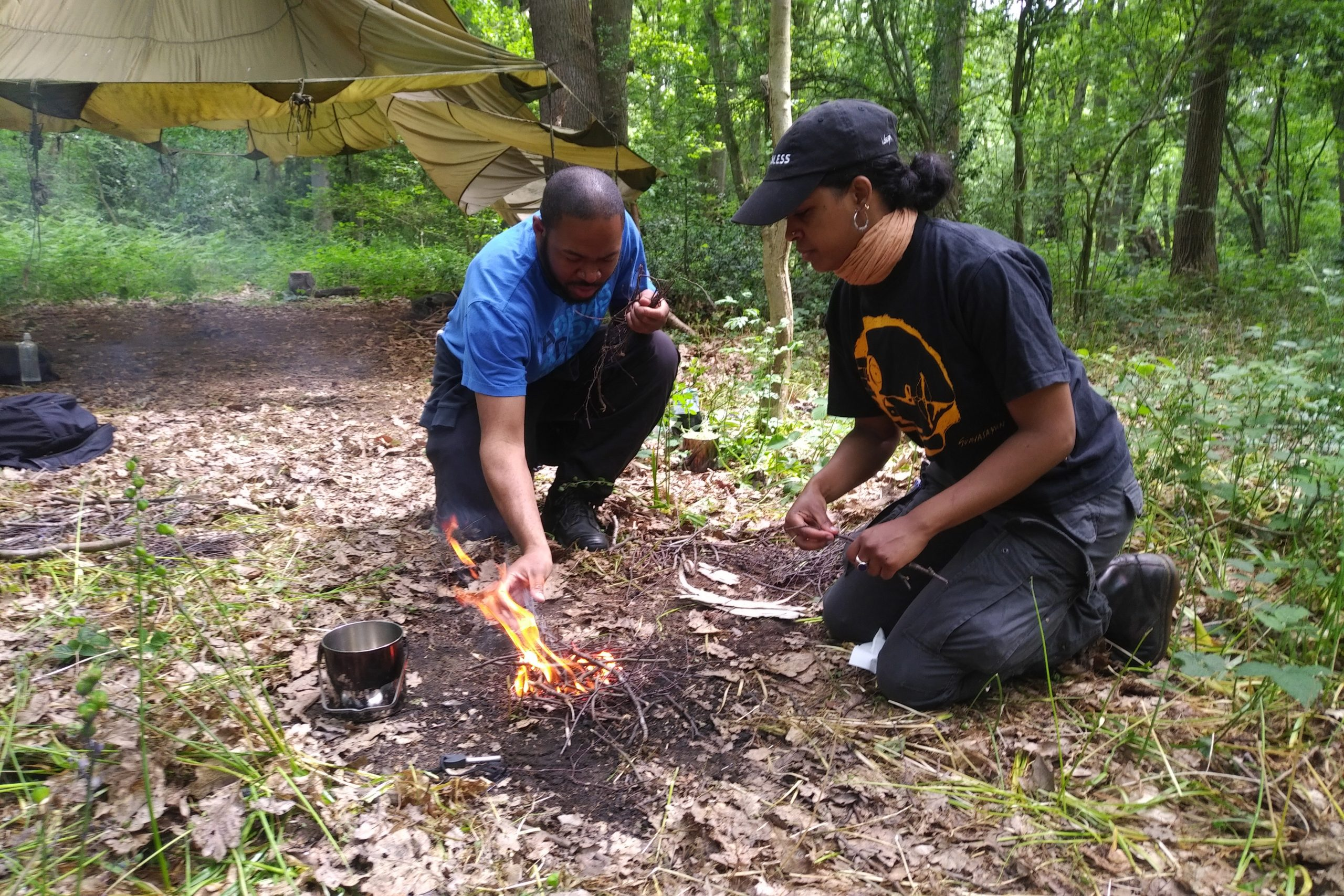 Two people building a camp fire in front of a tent in the woods. The man is wearing a blue t-shirt and dark waterproof trousers. The woman is wearing a black hat and t-shirt and waterproof trousers. They are kneeling on the ground.