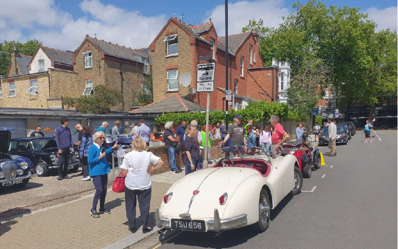 Residents standing around classic cars at the car show in the sunshine.