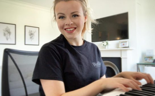 A blonde woman, Cate from Richmond performing arts school WestWay,, wearing a black t-shirt sitting playing a keyboard. Her blonde hair is tied up and she is turned to the camera smiling.