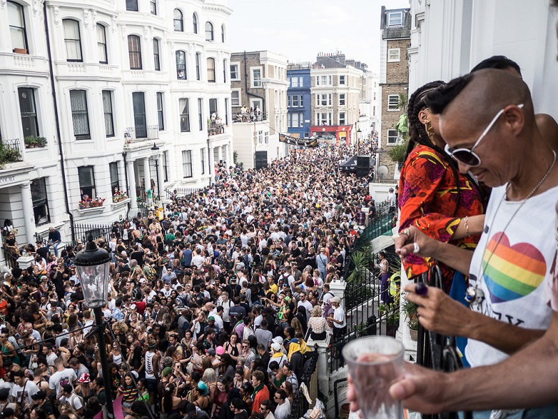 People looking over a balcony at a packed street of carnival goers. The person nearest the camera is wearing sunglasses and a t-shirt with a rainbow heart.