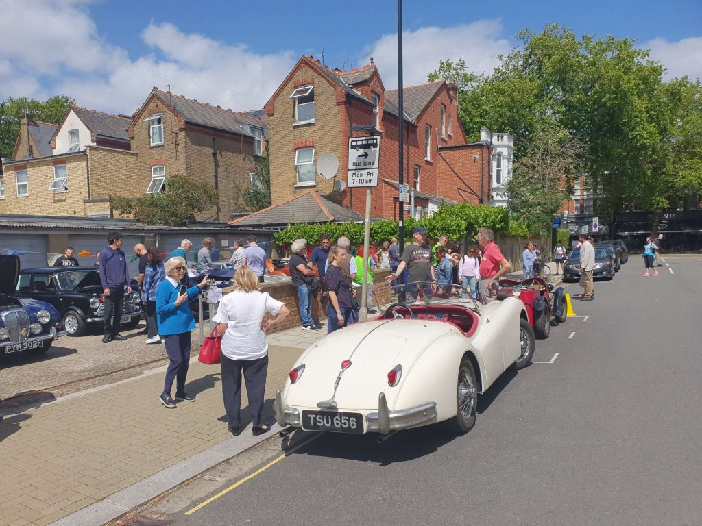 Residents standing around classic cars in the sunshine.