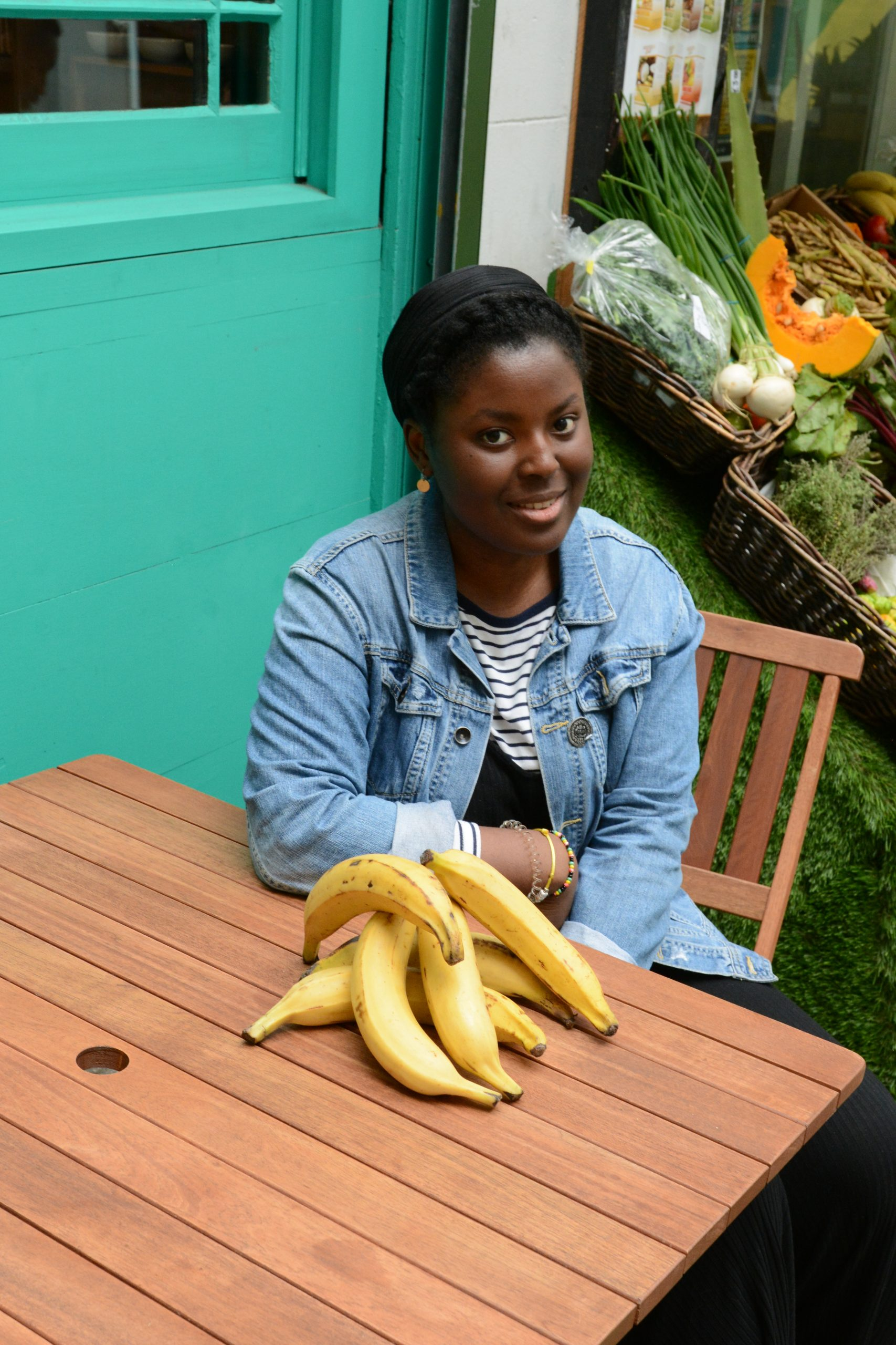 Tomi Makanjuola sits at a table. In front of her is a big bunch of plantains. Behind her there seems to be a fruit and veg stand.
