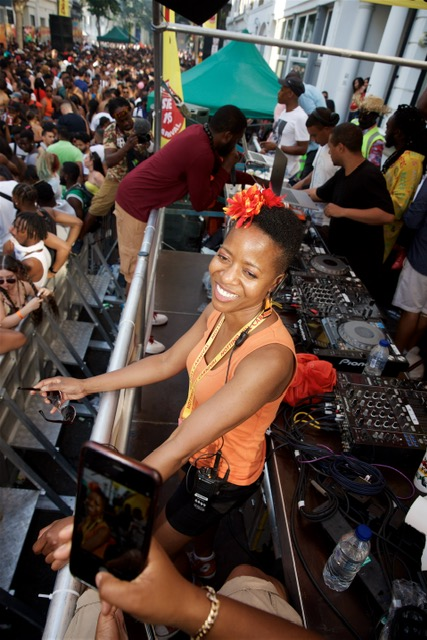 Linett Kamala smiles into a crowd. She is dressed in orange, with a flower in her hair. In the foreground, someone is holding up a phone to photograph her. Behind her are mixing decks.