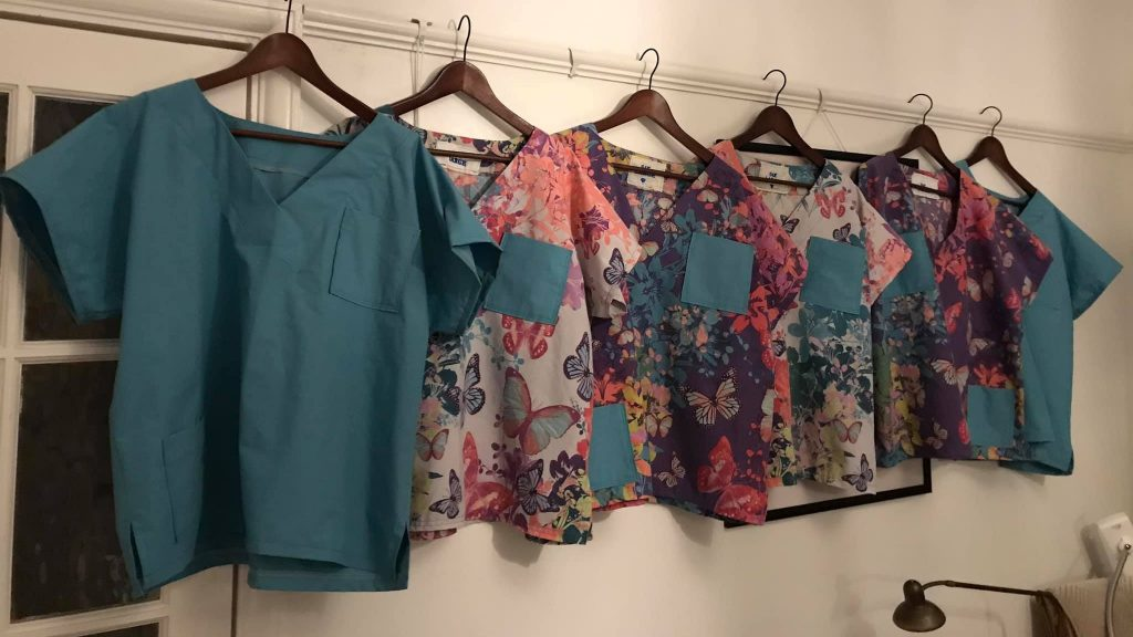 Hand-made hospital scrubs, all with different patterns, hanging up in a line.