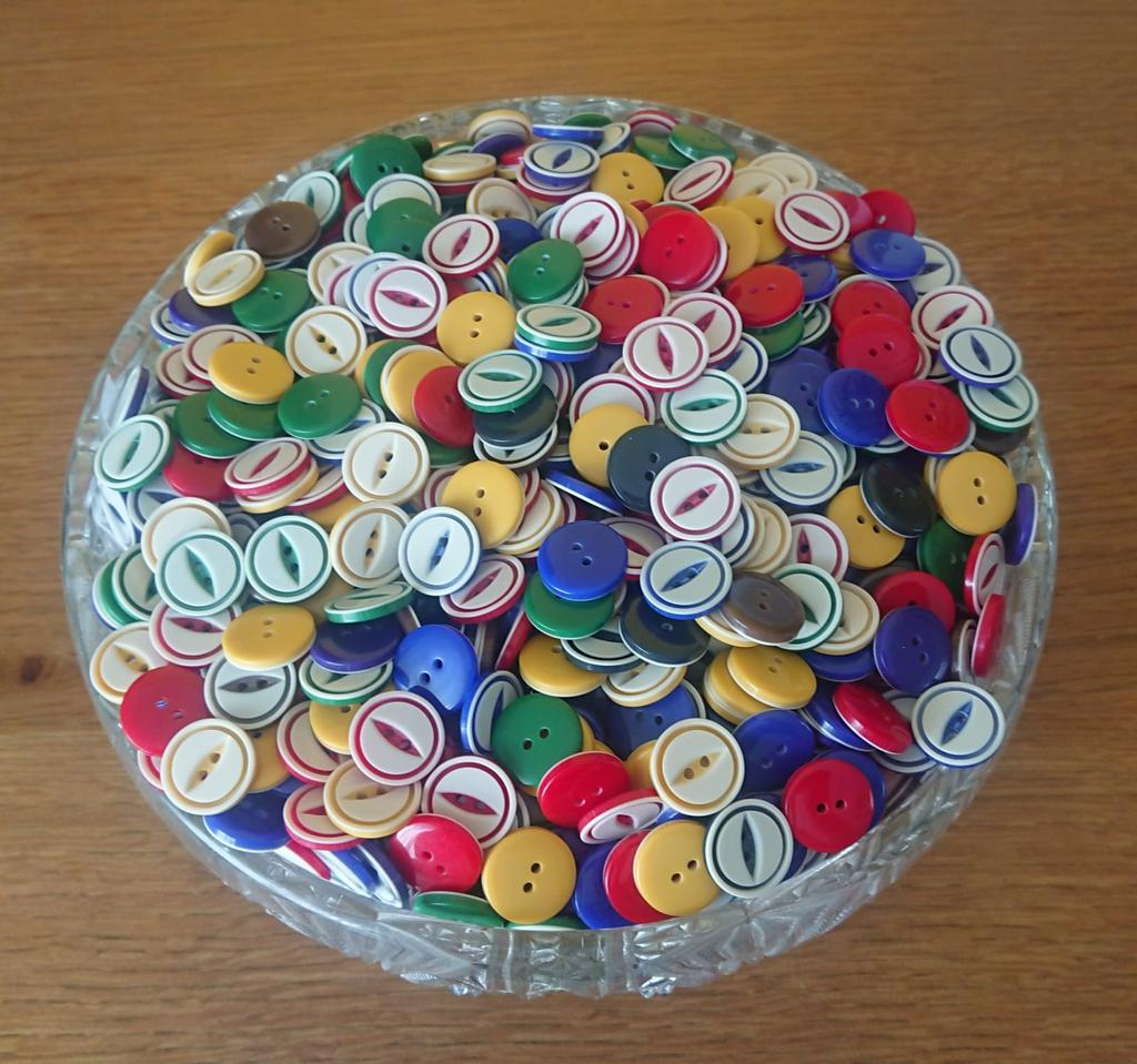 A large glass bowl full of buttons.
