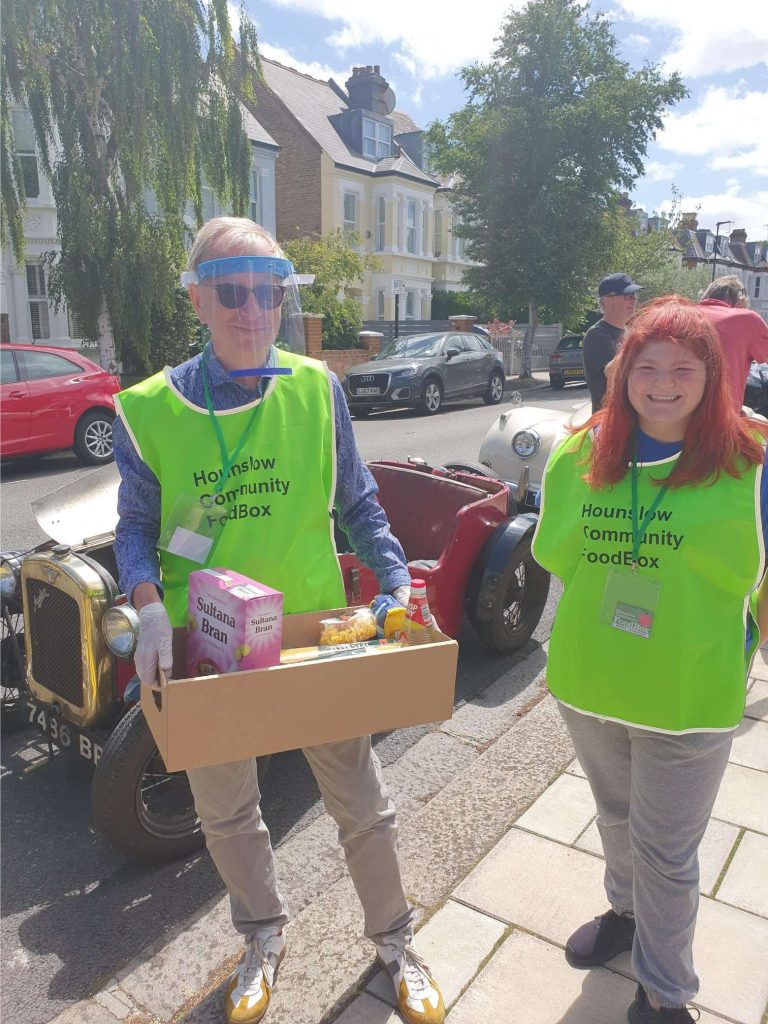 FoodBox volunteer Danielle with treasurer Philip Jones wearing high vis yellow vests. Philip is wearing a clear plastic visor over his face and is carrying a box full of supplied. They are standing in front of a red class Austin 7 car.