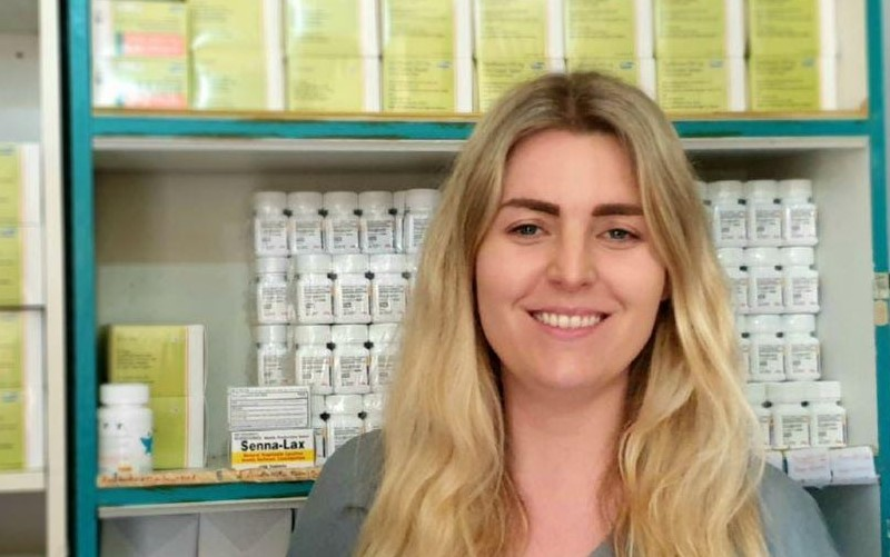 A blonde-haired lady who works for IHP miling in front of white and green boxes of medicine.