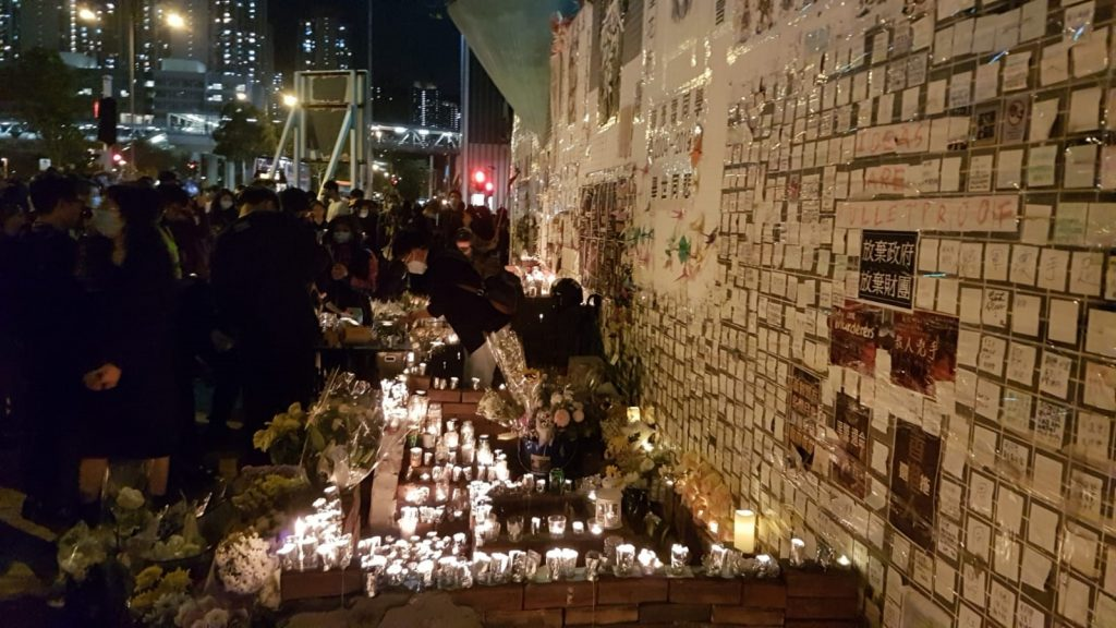 A crowd of people surrounding flowers and candles in the dark streets of Hong Kong.