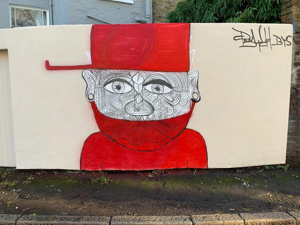 Psych's anti-knife mural on Stockwell Lane. The painting is of a man in a red mask and hat. There are lines all over his face, signifying identity.
