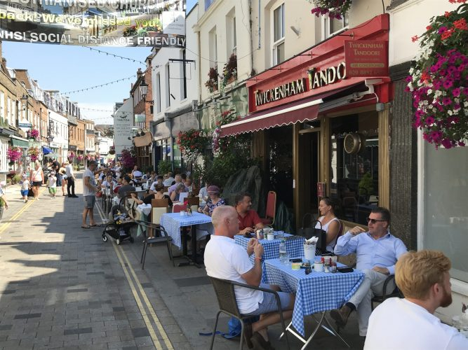 Lots of happy customers eating outside of restaurants in the sunshine in Twickenham because of the Eat Out to Help Out scheme.