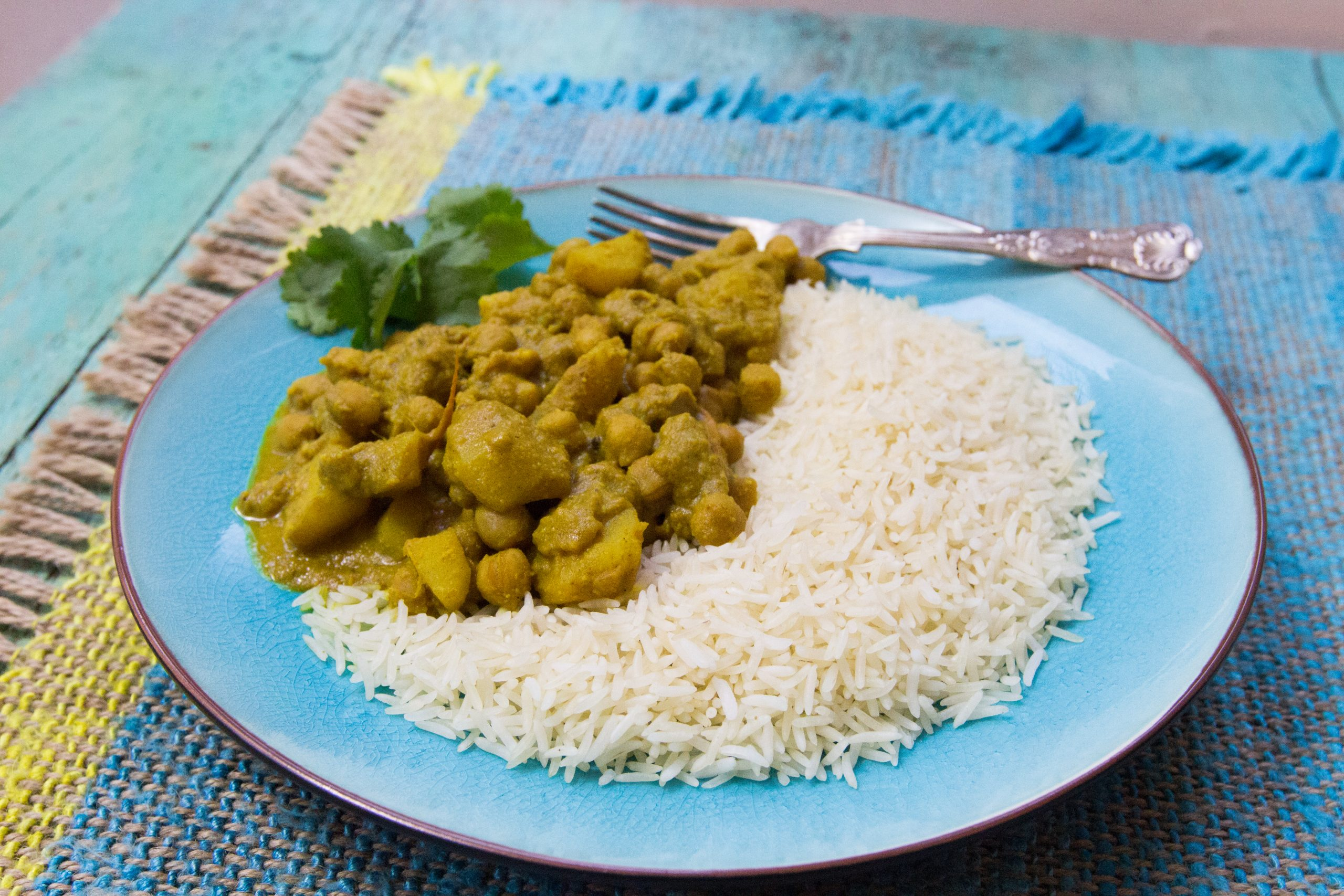 A chickpea curry with rice and a green garnish, set on a blue plate. There is an elegant silver fork sitting on the plate.