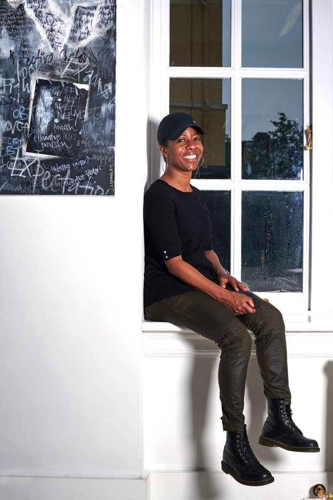 Linett Kamala, dressed in black, sitting in a white window, with her black and white artwork on the left. She is smiling.