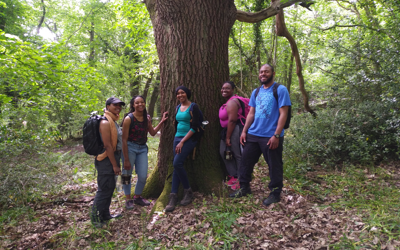 Wild in the City participants relax beneath a tree. They're wearing colourful clothes and have big grins on their faces