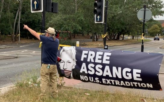 A protester talks into a megaphone in front of a banner saying Free Assange No US extradition