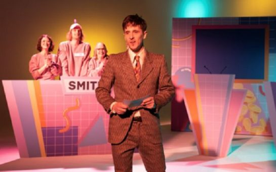 A man in a suit presents a game show with lurid pink and yellow lighting