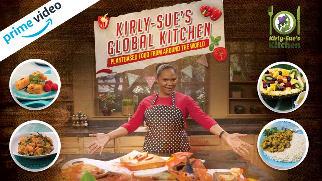 A promotional image for Kirly-Sue's Global Kitchen. She wears an apron and spreads her arms wide, smiling. Dishes that will appear on the show are superimposed over the photo e.g. a salad and a chickpea curry.