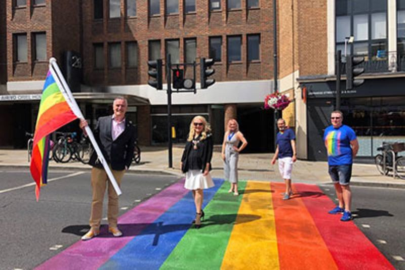 Five adults standing on the new Pride crossing in Richmond. The vertical lines stretch across the the whole road and are red, orange, yellow, green, blue and purple. One of the men is also carrying a large Pride flag. They all look happy and the sun is out.